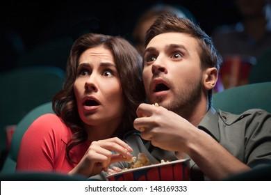 Película de terror. Pareja joven aterrorizada comiendo palomitas de maíz mientras ve la película en el cine