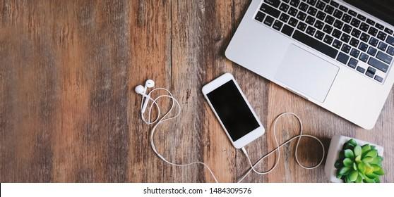 Flaches Laienfoto des Arbeitsplatzschreibtischs mit Laptop, Smartphone, Kopfhörern und grüner Pflanze mit hölzernem Hintergrund des Kopierraums, Banner für Website-Kopfzeile und Design für Text