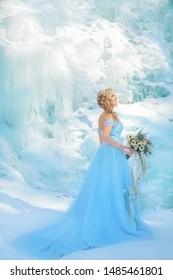 Wintermärchen auf einem Eiswasserfall Ein schönes Mädchen mit langen blonden Haaren und einem blauen Kleid mit einem langen Zug hält einen Blumenstrauß in der Hand ...