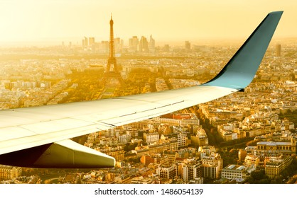Plane flies above Paris in summer evening, France. Aerial panoramic view of Eiffel tower from airplane window. The plane's wing over streets of Paris at sunset. Flight and air travel to Paris.