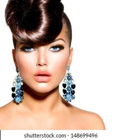 青い目とイヤリングのファッションモデルの女の子の肖像画。クリエイティブなヘアスタイル。髪型。化粧。白い背景で隔離の美女
