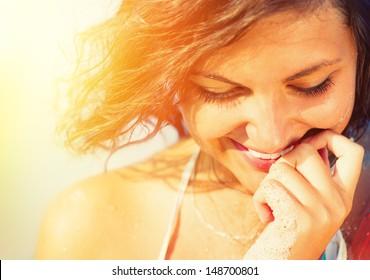 美容サンシャイン少女の肖像画。幸せな女笑顔と見下ろしています。ビーチの暑い太陽の下で日当たりの良い夏の日。