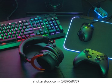 gamer work space concept, top view a gaming gear, mouse, keyboard, joystick, headset, mobile joystick, in ear headphone and mouse pad with rgb color on black table background.