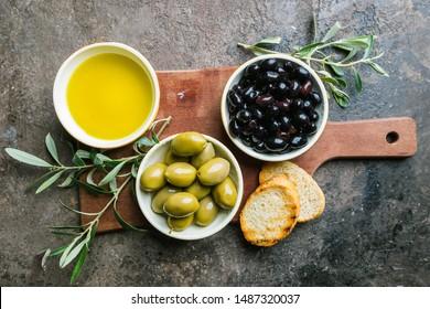 Un conjunto de aceitunas verdes y negras y aceite de oliva sobre un fondo de piedra oscura, vista superior