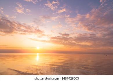 Ruhiges Meer mit Sonnenuntergangshimmel und Sonne durch die Wolken vorbei. Meditationsozean und Himmelhintergrund. Ruhige Seelandschaft. Horizont über dem Wasser.