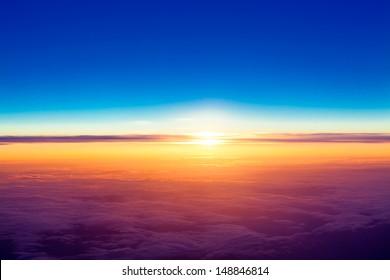 puesta de sol con una altura de 10000 km. Puesta de sol espectacular. Vista del atardecer sobre las nubes desde la ventana del avión
