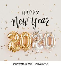 Feliz año nuevo 2020 celebración. Lámina de oro y plata globos número 2020 y confeti sobre fondo rosa. Lay Flat