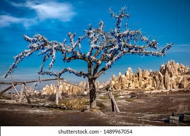 El árbol decorado con amuletos en forma de ojo (nazar) tradicionalmente se cree que protege contra los ojos malvados enmarca un fondo de chimeneas de hadas formadas de roca blanda en la antigua Capadocia (Kapadokya)