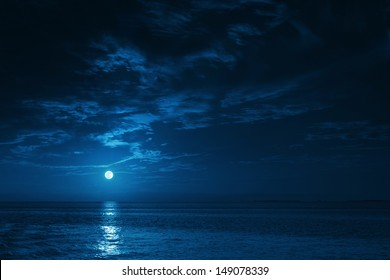 Esta ilustración fotográfica de un océano azul profundo iluminado por la luna por la noche con olas tranquilas sería un excelente fondo de viaje para cualquier región costera o vacaciones.