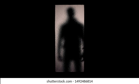Silhouette of robber or maniac standing behind glass door, phobias and fears
