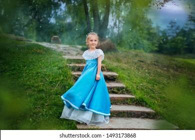 青いレトロなドレスを着た白い髪の少女。おとぎ話の王女が階段に立っている
