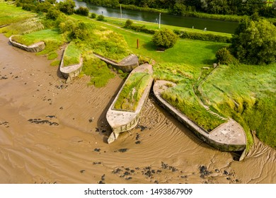 Aerial drone view of silt filled hulks of abandoned boats used to reduce erosion on the banks of the River Severn in England (Purton Hulks)