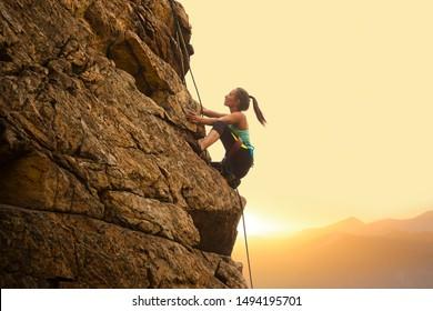 Schöne Frau, die auf dem hohen Felsen am nebligen Sonnenuntergang in den Bergen klettert. Abenteuer- und Extremsportkonzept