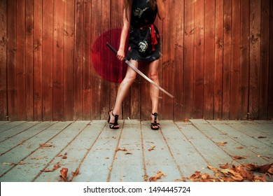 Girl with sword and Japanese dress outdoors behind wooden fence