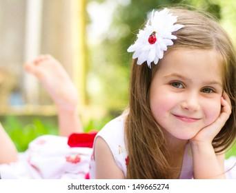 緑の草の上に横たわって笑顔の少女の肖像画