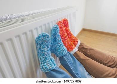 Familie in warme gebreide wollen sokken in de buurt van een huisverwarmer in koude wintertijd. Het symbolische beeld van het stookseizoen in huis. Een deel van het lichaam, selectieve aandacht.