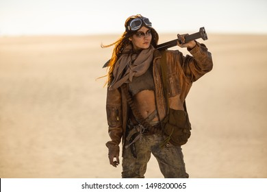 Post-apocalyptic woman with weapon outdoors. Young slim girl warrior in shabby clothes holding sword standing in a confident pose looking away. Nuclear post-apocalypse time. Life after doomsday