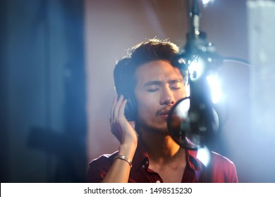 young asian musician singer singing song in recording studio
