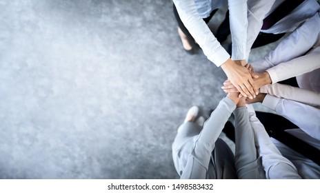 Schließen Sie herauf Draufsicht der jungen Geschäftsleute, die ihre Hände zusammenstellen. Stapel Hände. Einheits- und Teamwork-Konzept.