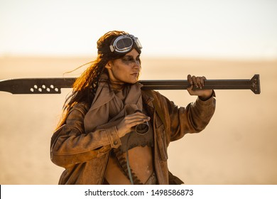 Post-apocalyptic woman warrior with weapon outdoors. Attractive fichter girl in shabby clothes holding sword and binoculars standing in a confident pose looking away. People in nuclear post-apocalypse