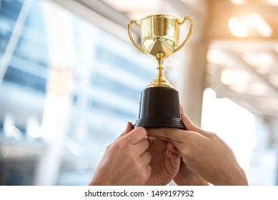 Goldene Trophäe des Siegers für Sieger mit den Händen des Sportspielers im Hintergrund des Sportstadions. Erfolgs- und Leistungskonzept. Thema Sport- und Pokalpreis. American Football Award und Match Game Play Preis