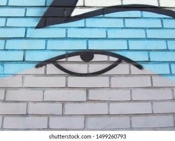 レンガの壁に落書きの目。現代のストリートアート。表情豊かな表情。