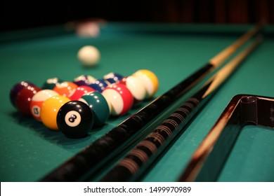 Juego deportivo de billar sobre un paño verde. Bolas de billar multicolores en forma de triángulo con números, dos tacos, una bola blanca y un triángulo en una mesa de billar. Billar bolas de billar de cerca.