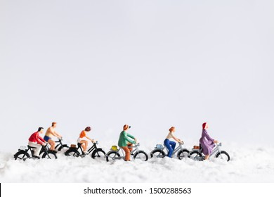 Miniature people : Travelers riding a bicycle on snow , winter background concept