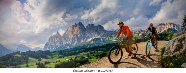 Pareja en bicicleta en bicicleta eléctrica, paseos por senderos de montaña. Mujer y hombre en bicicleta en el paisaje de las montañas Dolomitas. Pista de ciclismo e-mtb enduro trail. Actividad deportiva al aire libre.