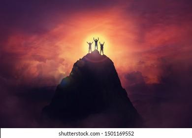 Gemeinsam Hindernisse überwinden als Gruppe von drei Personen, die auf einem Berg die Hände heben. Feiern Sie Sieg und Erfolg über Sonnenuntergang Hintergrund. Zielerreichungssymbol.