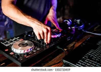 DJ spielt Live-Set und mischt Musik auf der Plattenspieler-Konsole auf der Bühne im Nachtclub. Disc Jokey Hände auf einer Soundmixer-Station bei einer Clubparty. DJ Mixer Controller Panel zum Abspielen von Musik und Feiern.