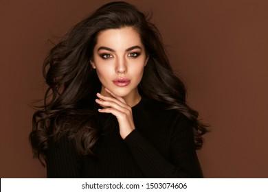 茶色の目と健康的な長い光沢のある波状の髪型を持つブルネットの髪の女性の肖像画。ボリュームシャンプー。ブラックカーリーパーマヘアと明るいメイク。ビューティーサロンとヘアケアのコンセプト。