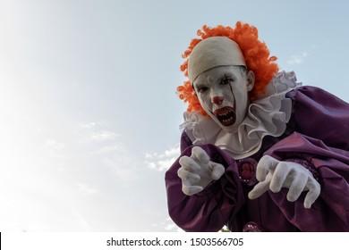 Chico adolescente disfrazado de payaso con dientes afilados. Cosplay para celebrar Halloween o una fiesta de disfraces de héroes terribles. Fondo de cielo, espacio de copia.