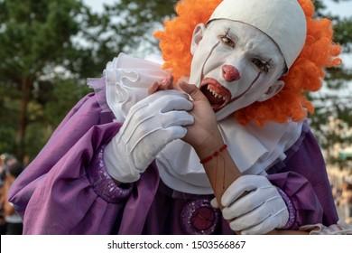 Cosplay de Halloween o festival de héroes de terror. Un adolescente con un disfraz de payaso malvado con dientes afilados finge morder la mano de alguien. Maquillaje de calle en un chico