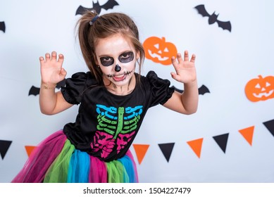Retrato de una niña niño con maquillaje de calavera de azúcar en un traje de esqueleto sobre fondo blanco con murciélagos y calabaza.