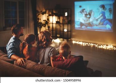 家族の母親の父と子供たちが家で夕方にプロジェクター、テレビ、ポップコーンと一緒に映画を見ています