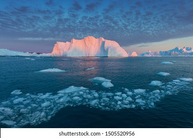 Iceberg at sunset. Nature and landscapes of Greenland. Disko bay. West Greenland. Summer Midnight Sun and icebergs. Big blue ice in icefjord. Affected by climate change and global warming.