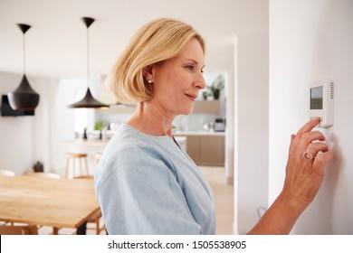 Close Up van rijpe vrouw centrale verwarming temperatuur thuis op thermostaat aanpassen