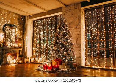 warme gemütliche magische Abend in Luxus alten Weihnachtszimmer Märchen Innenarchitektur, Pahorama-Fenster, Kamin Weihnachtsbaum von Lichtern, Geschenken, Kerzen, Laternen, Girlanden Beleuchtung geschmückt. Neujahrsfeiertage