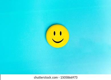 Positives lustiges Smileygesicht auf einem türkisfarbenen Kartonhintergrund. Kopieren Sie Platz für Werbung und Texte