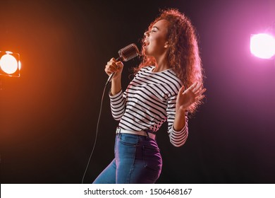 Beautiful African-American female singer with microphone on stage