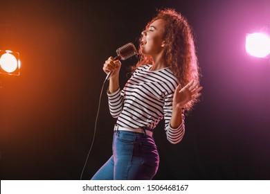 ステージにマイクを持った美しいアフリカ系アメリカ人の女性歌手