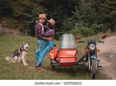 Paar verliebt in Händchenhalten auf Naturreisen mit Husky-Hund in den Bergen. Junge Leute glücklich zusammen. Liebhaber küssen Porträt im Urlaub oben.