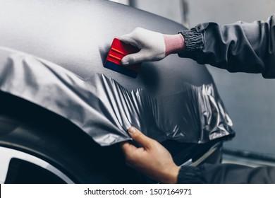 Spezialist für Autoverpackungen, der Vinylfolie oder Folie auf das Auto legt. Selektiver Fokus.