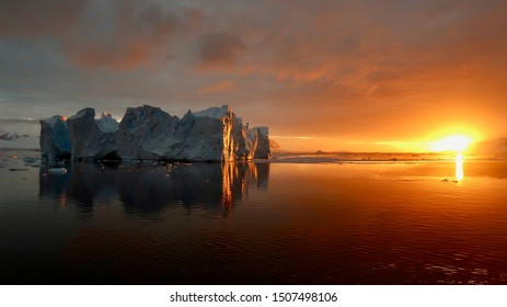 Iceberg seen at sunset in Antarctica, with sunlight reflecting on the iceberg, with orange clouds and a sea colored by the sun, and the iceberg reflecting in the water