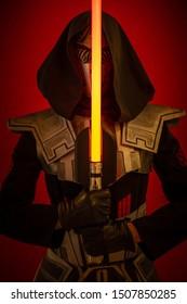 Acteur un homme dans un masque et en costumes de personnages fantastiques fictifs posant sur fond rouge