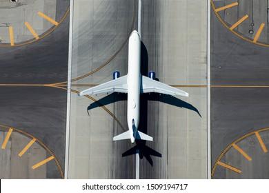 Luftaufnahme eines Flugzeugs mit schmalem Körper, das die Landebahn des Flughafens verlässt.