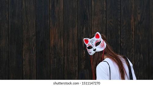 Mädchen im Masken-Anime-Stil. Asiatische Katzenmannmaske, Kitsune-Maske des Japanischen. Festival der japanischen Kultur. Jugend-Subkultur, informeller Stil. Speicherplatz kopieren