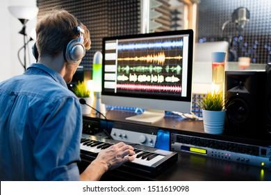 コンピューターのモニターのそばに座って音で作業しながらピアノキーボードのキーを押すヘッドフォンを持つ若いミュージシャン