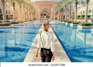 Disfrutando de viajar en los Emiratos Árabes Unidos. Mujer joven con cámara caminando por el centro de Dubai.